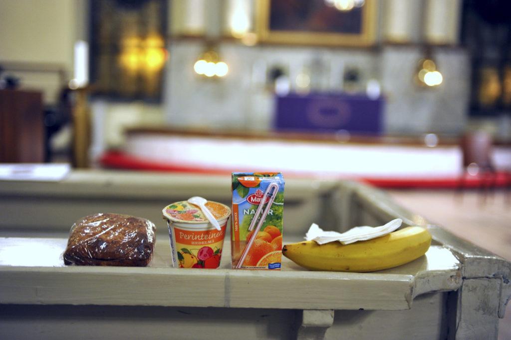 Sämpylä, mehu ja banaani kirkon penkin selkänojalle aseteltuna